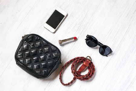 accesories: Close-up of Clothing and fashion accessories on wooden table,bag, belts, sunglasses, telephone, mobile phone, lipstick Stock Photo