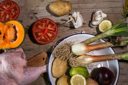 spiced: Uncooked spiced chicken and vegetables on kitchen table.From above Stock Photo