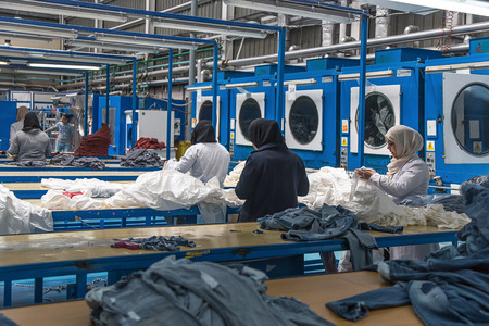 Tangier, Morocco-April 18,2016:In the picture we can see an industrial laundry with workers, washing machine, dryers, laboratory and boilers.