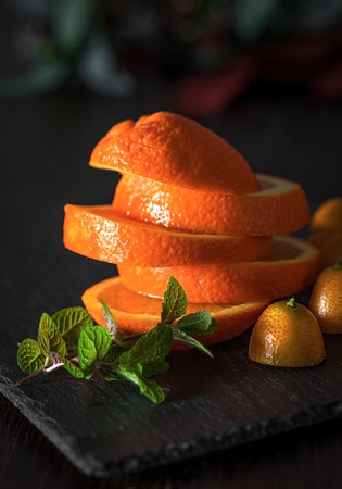 segments: Still life of cut segments of orange with halved tangerines and branch of mint