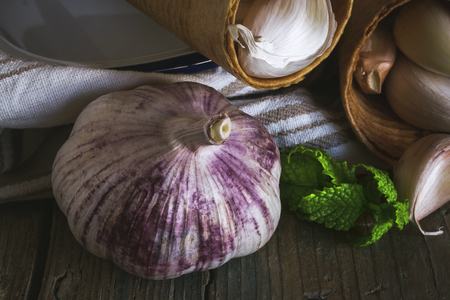 garlics: Purple garlics on a napkin on a rustic wooden table with thyme and parsley Stock Photo