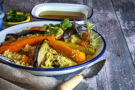 couscous: Traditional Moroccan Couscous ingredients and  Side Dish Served in Ornate Bowl on Top of Decorative Napkin and Rustic Wooden Table