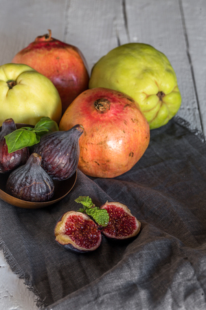 quinces: Fresh quinces and pomegranates on wooden table with napkin