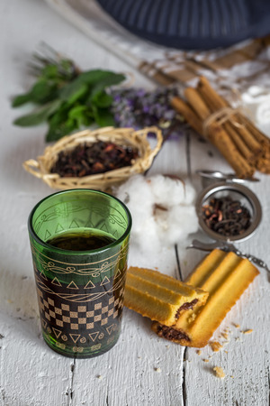 Arabic nana mint tea in traditional glass with mint, cinnamon, anise stars and almond and chocolate cake