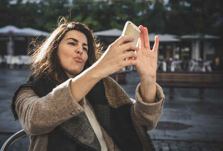 40 year old woman: Attractive 40 year old brunette woman taking selfie on the street Stock Photo