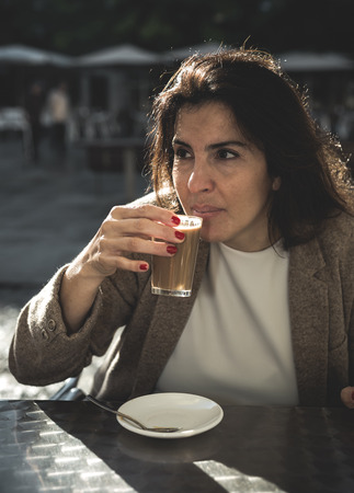 40 year old woman: 40 year old woman drinking coffee on the terrace of a backlit bar