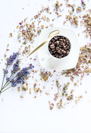 teaspoon: Cup of coffee beans on white background with teaspoon and flowers