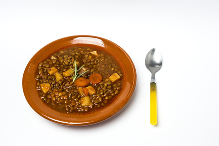 upholstered: Stew of lentils with sausage and pork. Typical Spanish food. With spicy chillies.Isolated Stock Photo