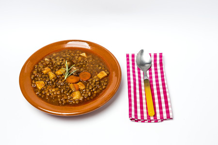 Stew of lentils with sausage and pork. Typical Spanish food. With spicy chillies.Isolated Stock Photo