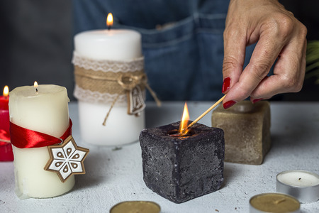enveloping: Unrecognizable woman hands lighting candles Christmas days, preparing the decoration
