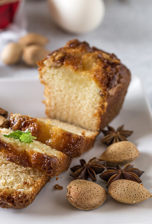 Homemade cinnamon cake and almonds on white table. Oxide