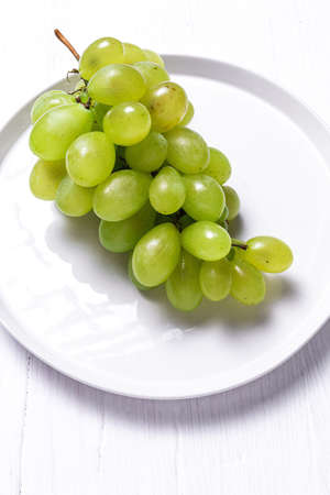 Fresh seasonal grapes in plate ready to eat On white background. Healthy food. Vegan food concept 스톡 콘텐츠