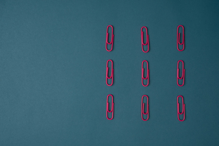 paperclips: Close-up of pink paperclips on blue background Stock Photo