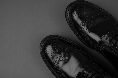 men s feet: The pair of black leather shoes on a black background