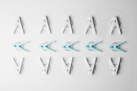 disorganized: Laundry clips organized over white background, top view