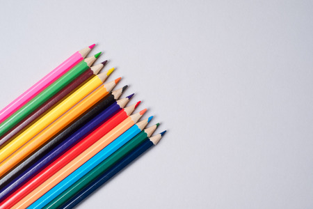 Colorful crayon pencils organized in a row over a white background, above view Stock Photo