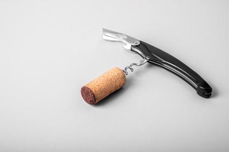 Wine cork and bottle opener on white background