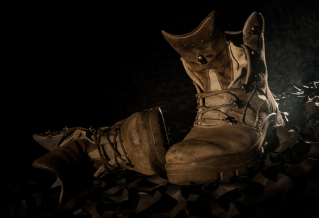 army boots: military boots on camouflage net and black backround