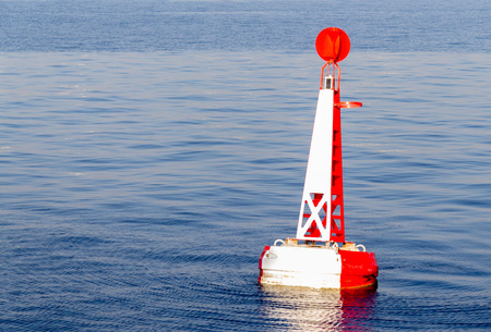 red white moored buoy in blue ocean Stock Photo