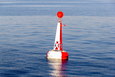 red white moored buoy in blue sea