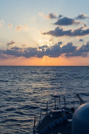 decommissioning: navy cannon on sunset in the sea Editorial