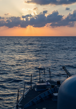 decommissioning: german navy cannon on sunset in the sea Editorial
