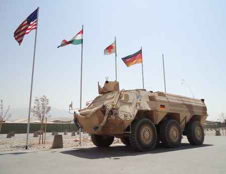 armored: german armored ambulance vehicle  fuchs  in front of national flags