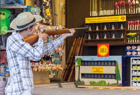 german handgun: a german man fires with a gun on a shooting gallery on amusement park Stock Photo