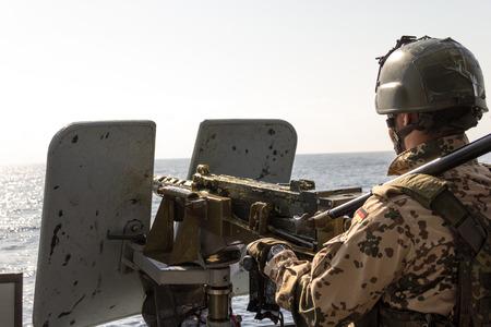 german soldier: German soldier on machine gun on a speedboat Stock Photo