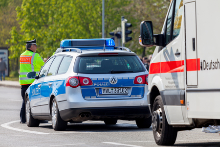 cross street with care: ALTENTREPTOW  GERMANY - 1. MAY 2016: german emergency ambulance and police vehicle stands on the street in altentreptow on may 2016.