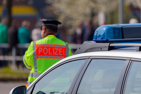 light duty: ALTENTREPTOW  GERMANY - 1. MAY 2016: german police vehicle and policeman stands on the street in altentreptow on may 2016.
