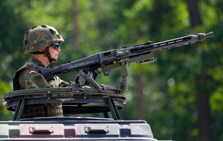 german soldier: BURG  GERMANY - JUNE 25, 2016: german soldier secures with machine gun a zone on open day in barrack burg  germany at june 25, 2016