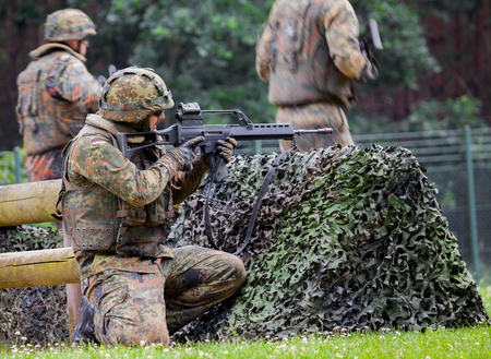conscription: BURG  GERMANY - JUNE 25, 2016: german soldier fires with hk g 36 rifle, on open day in barrack burg  germany at june 25, 2016 Editorial
