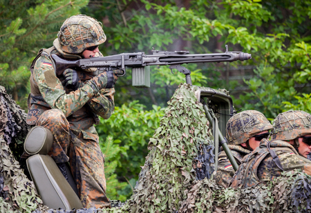 conscription: BURG  GERMANY - JUNE 25, 2016: german soldier fires with machine gun, on open day in barrack burg  germany at june 25, 2016