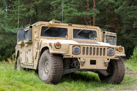 armored truck: military vehicle stands on green terrain Editorial