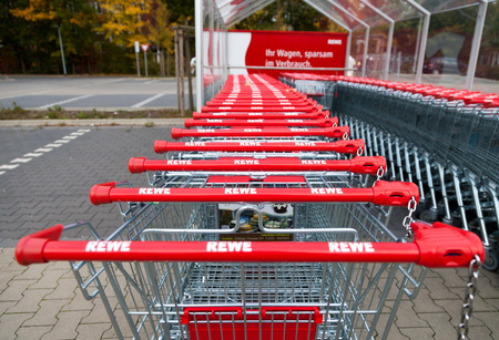 HANNOVER / GERMANY - OCTOBER 18, 2016: Shopping carts of the german supermarket chain, Rewe stands together in a row on parking area.