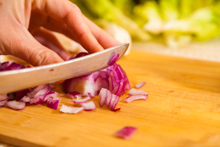 cropped: cropped onion with other vegetables on a cutting board