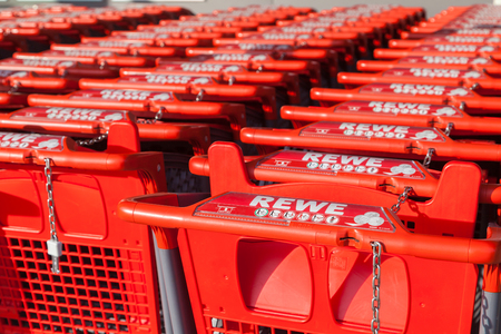 co operative: BURG  GERMANY - NOVEMBER 13, 2016: Shopping carts of the german supermarket chain, REWE stands together in a row. The REWE Group is a German diversified retail and tourism co-operative group.