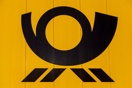 posthorn: HANNOVER  GERMANY - NOVEMBER 27, 2016: german mail service ( Deutsche Post ) logo on a yellow container Editorial