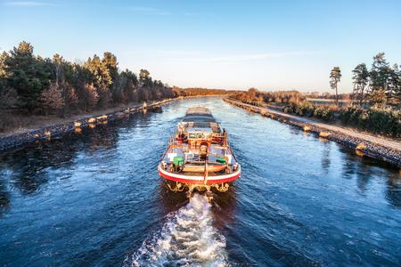 binnenvaartschip drijft een gracht langs de rivier