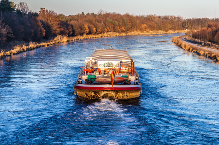 inland vessel drives a canal river along Stock Photo