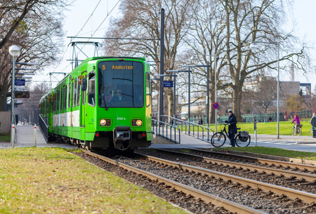 HANNOVER  GERMANY - MARCH 12, 2017: german tram from UESTRA drives to the next stop. UESTRA is the operator of public transport in the city of Hanover, Germany
