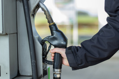 hand on a gas pump nozzle Stock Photo