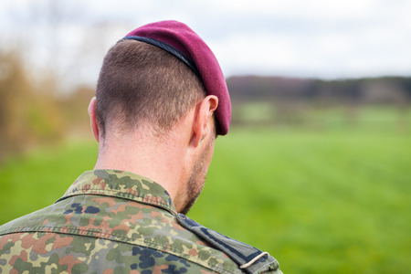 german soldier with a beret stands on a field background