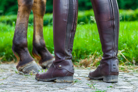 jackboots: a horsewoman in riding boots near a horse
