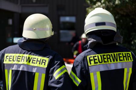 German fireman ( Feuerwehr ) stands near an accident 写真素材