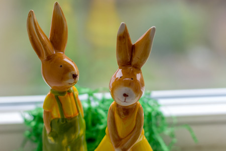 two decoration rabbits stand near a window