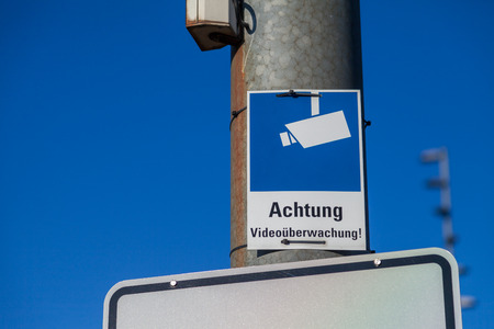 monitoring camera sign hangs on a lamp pole. Achtung Videoueberwachung means caution video control