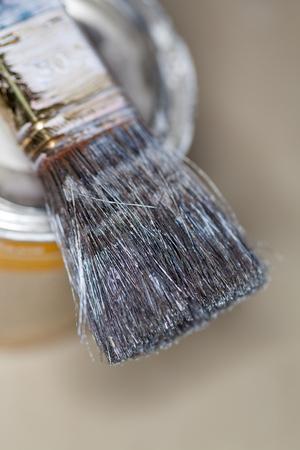 a paint brush lies on a paint pot Standard-Bild