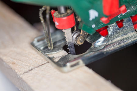 a green jigsaw saws a bright plank Standard-Bild